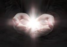 Ljus i händer - be korset royaltyfria bilder