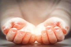 Ljus i kvinnas händer Begrepp av att dela och att ge sig, nytt liv Arkivbild