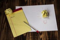 Ljus idé som dras på den pappers- pennanteckningsboken Arkivfoto