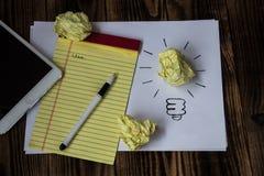 Ljus idé som dras på den pappers- pennanteckningsbokminnestavlan Royaltyfria Foton