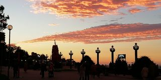 Ljus kontrastera bakgrund av havssolnedgången Den mörka konturn av invallningen av sjösidastaden royaltyfria bilder