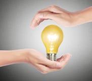 Ljus kula, idérik idé för ljus kula i handen Arkivbild