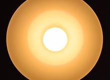 Ljus kula som är upplyst i en hängande lampa som underifrån beskådas Arkivbild
