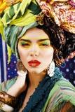 Ljus kvinna för skönhet med idérikt smink, många sjalar på huvud l royaltyfri bild