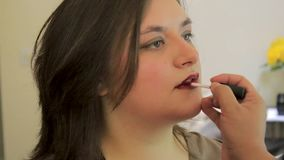 Ljus läppstift som appliceras till den unga kvinnan stock video