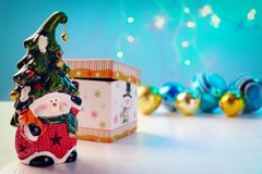 Ljus leksakdvärg med en gladlynt framsida och en klocka på de skinande bollarna för lock, ask på vit bakgrund arkivbilder
