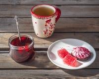 Ljus lunch med sötsaker, te i ett stort keramiskt rånar och en exponeringsglaskrus med körsbärsrött driftstopp och en lantlig sti royaltyfria foton