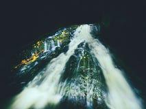 Ljus målning i nattvattenfall i höstström Suddigt skummande vatten på mossigt vaggar med färgrika sidor Royaltyfri Bild