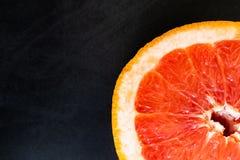 Ljus ny grapefrukt på en svart bakgrund arkivbilder