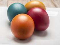 Ljus och gladlynt påskstilleben med regnbågefärgägg Fotografering för Bildbyråer