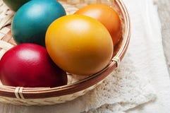 Ljus och gladlynt påskstilleben med regnbågefärgägg Arkivbilder
