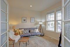 Ljus och hemtrevlig vardagsrum med elfenbenväggar royaltyfri foto