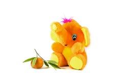 Ljus orange leksakelefant och tangerin Arkivfoton