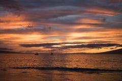 Ljus orange solnedgång i moln och havet Arkivbild