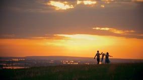 Ljus orange solnedgångfamilj med lite pojken som vilar i naturen, hållhänder stock video
