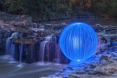 Ljus Orb som förbiser vattenfallen royaltyfri fotografi