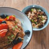 Ljus platta med amerikanska pannkakor f?r en sund sommarfrukost med b?r och en maktbunke som g?ras av naturlig yoghurt arkivfoton