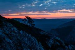 Ljus röd gryning i bergen i en blåsig molnig morgon, stiger solen från horisonten arkivfoto