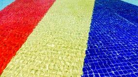 Ljus - röd, gul och blå randigt mosaikgolv för blått, av springbrunnen som täckas med vatten Arkivfoto