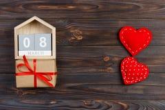 Ljus röd hjärta på träkvarterkalender med gåvaasken, 8 mars som firar internationell dag för kvinna` s Royaltyfri Fotografi