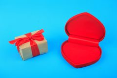Ljus röd hjärtaask och gåva som slås in med det röda bandet på blå bakgrund royaltyfria foton