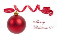 Ljus röd julgranboll med det lockiga bandet royaltyfri foto