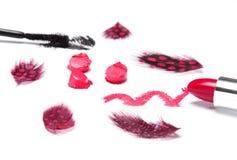 Ljus röd läppstift med svart mascara och fläckiga fjädrar Arkivfoton