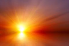 Ljus röd solnedgång med sunstrålar Arkivfoto