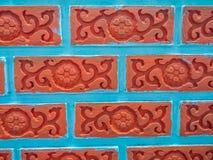 Ljus röd tegelsten med blommamurgrönan mönstrade väggbakgrund Fotografering för Bildbyråer