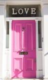 Ljus rosa dörr på en vit vägg med förälskelse överst Arkivbild