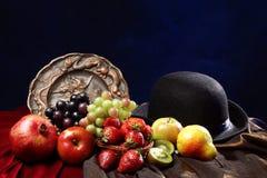 Ljus saftig frukt i den klassiska holländska stilleben bredvid en bunkehatt och en gammal inristad maträtt Arkivfoton