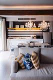 Ljus signalsoffasoffa och färgglade kuddar i vardagsrum med äta middag område arkivbilder