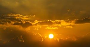 Ljus sol i en orange himmel med mörka moln Royaltyfri Fotografi