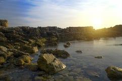 Ljus sol och den steniga stranden royaltyfri fotografi