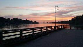 Ljus solnedgång på pir Arkivfoto