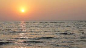 Ljus solnedgånghimmel med en solbana till havet på bakgrunden av havet stock video