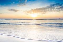 Ljus soluppgång över på stranden Arkivfoto