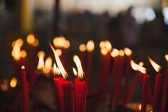 Ljus stearinljus som ljust bränner i den svarta bakgrunden Arkivfoton