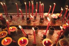 Ljus stearinljus som ljust bränner i den svarta bakgrunden Royaltyfri Bild