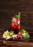 Ljus uppfriskande jordgubbecoctail med mintkaramellen, is, skivor av limefrukt och stycken av jordgubben Sommardrycker kopiera av Royaltyfri Foto