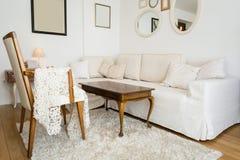 Ljus vardagsrum med den vita soffan och tappningdekoren arkivbild