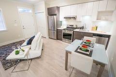 Ljus vardagsrum med kök- och matställetabellen royaltyfria foton