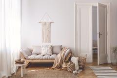 Ljus vardagsrum som var inre med unika handgjorda korgar, gjorde av naturliga material och en hemtrevlig träsoffa med beigea kudd fotografering för bildbyråer