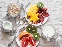 Ljus vattenfärgstilleben Variation av frukter - den mango-, kiwi-, grapefrukt-, apelsin- och grekyoghurten, havre flagar på en lj arkivbilder