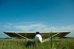 Ljus vit flygplanslandning på en grön äng, trans. som är utomhus- Royaltyfri Fotografi