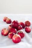 Ljusa äpplen för sken på en vit bordduk arkivfoton