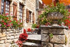 Ljusa blomkrukor på ett forntida stenhus i Frankrike Arkivbilder
