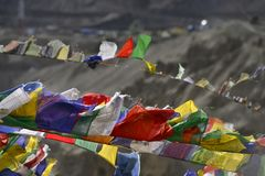 Ljusa buddistiska bönflaggor framkallar i vinden mot bakgrunden av berget Arkivbild