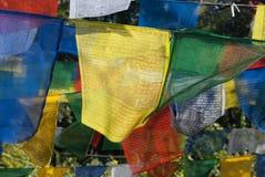 Ljusa buddistiska bönflaggor, i mitt av flaggan är en ljus gul färgtorkduk Royaltyfri Bild