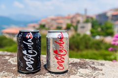 Ljusa cans för för Korsika Cola och Cola på väggen i Sartene Korsika Frankrike Royaltyfri Bild